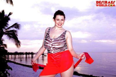 Plump pornstar Desirae demonstrating massive saggy boobs outdoors on beach